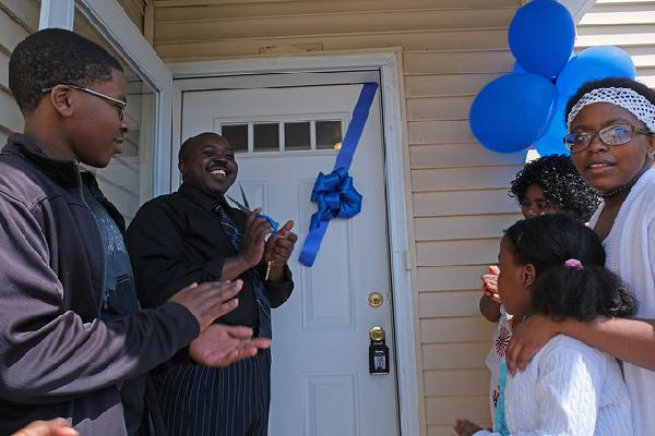 Janvier cuts the ribbon on his new front door